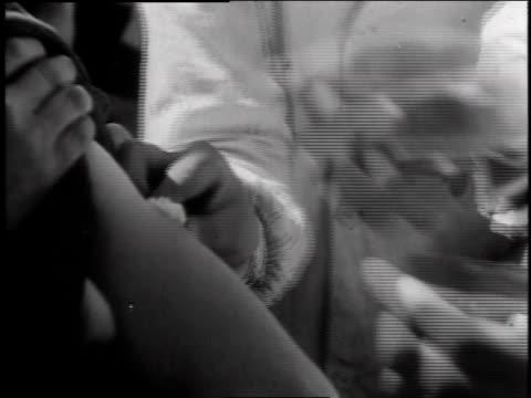 vídeos y material grabado en eventos de stock de doctor injecting patient in arm / patient holding cotton to injected area - 1947