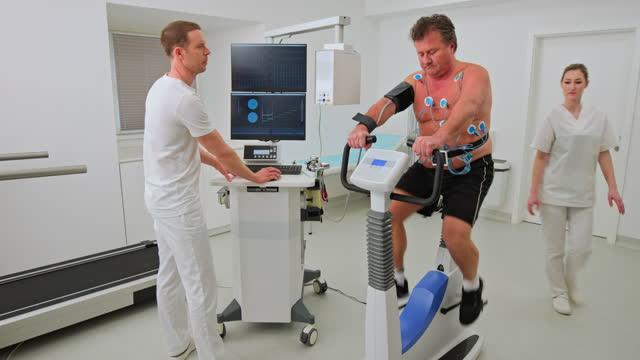 心臓ストレステストを受けている中年男性の看護師に電極を調整するように指示する医師 - 電極点の映像素材/bロール