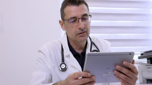 doctor interpreting medical test results on tablet to patient - part of a series stock videos & royalty-free footage
