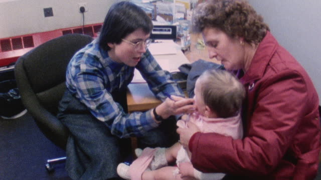 1983 montage doctor iona heath performing examination for a baby and mother / london, england - female doctor stock videos & royalty-free footage
