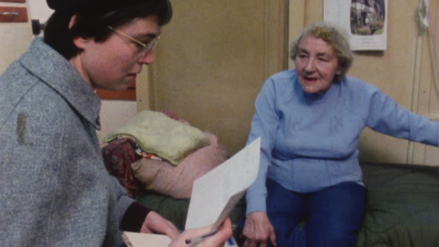 1983 montage doctor iona heath performing home visit in a patient's apartment / london, england - visita a domicilio video stock e b–roll