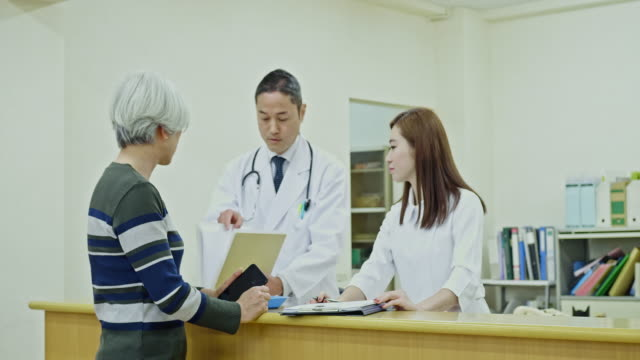 doctor joining the conversation at hospital with patient and nurse - mixed age range stock videos & royalty-free footage