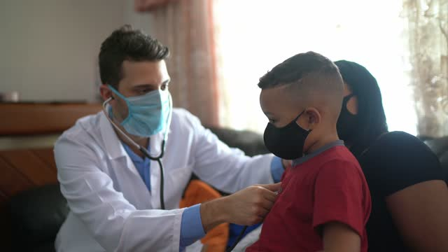 doctor listening to boy heartbeat during home visit - wearing face mask - visit stock videos & royalty-free footage