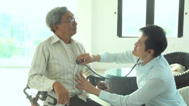 Doctor listening to elder patient's heart