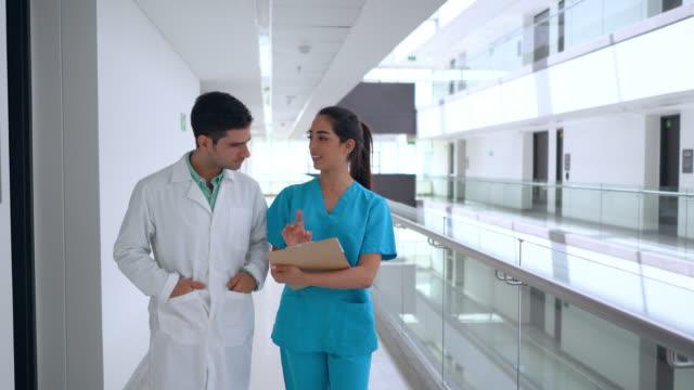 彼女はクリップボードを持っている間、看護師に耳を傾け、病院の廊下を歩くケースを議論する医師 - 親睦会点の映像素材/bロール