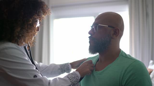 vídeos y material grabado en eventos de stock de médico escuchando los latidos del corazón del paciente durante la visita domiciliada - estetoscopio