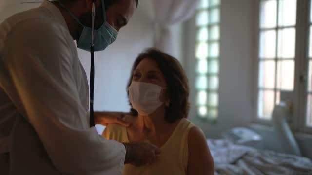 medico che ascolta il battito cardiaco del paziente durante la visita a casa - indossando la maschera facciale - apparato respiratorio video stock e b–roll