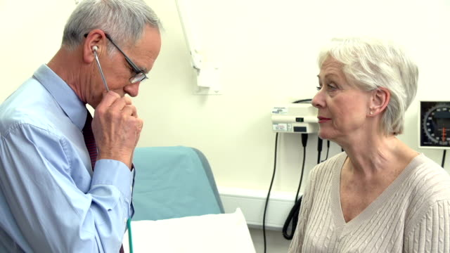 Doctor Listening To Senior Female Patient's Chest