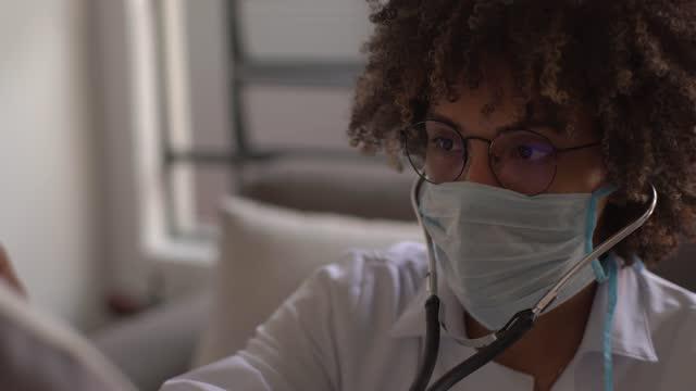 vídeos y material grabado en eventos de stock de médico escuchando latidos cardíacos de pacientes mayores durante una visita a casa - usando una máscara facial - estetoscopio