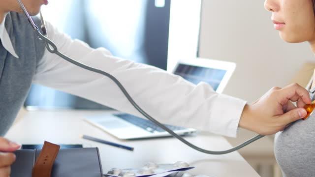 vídeos de stock, filmes e b-roll de médico ouvir pluse do paciente jovem - estetoscópio