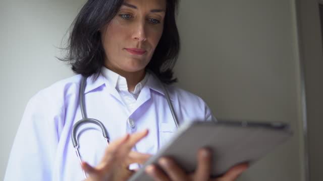 stockvideo's en b-roll-footage met arts kijken naar digitale tablet, close-up - positieve emotie