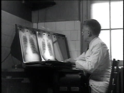 stockvideo's en b-roll-footage met 1946 ms doctor looking at x-rays and speaking into recording device / united states - kleine groep dingen