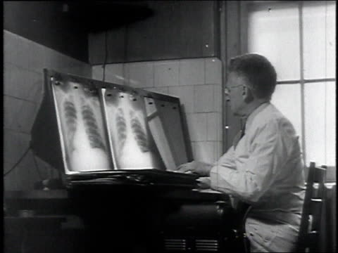 stockvideo's en b-roll-footage met 1946 ms doctor looking at x-rays/ usa - medische röntgenfoto