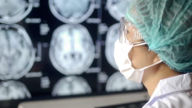 vídeos de stock e filmes b-roll de doctor looking ct examination image at computer monitor - tomografia