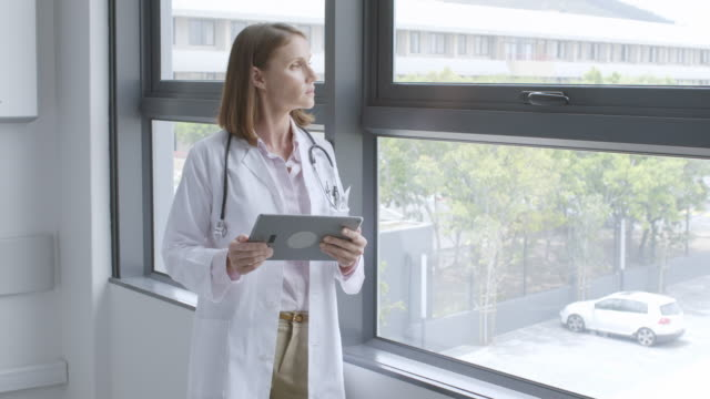 Doctor looking through window and using tablet pc