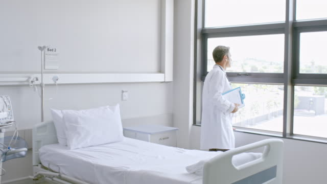 Doctor looking through window at hospital ward