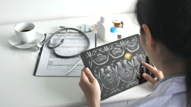 doctor looking x-ray image on digital tablet - clinic stock videos and b-roll footage