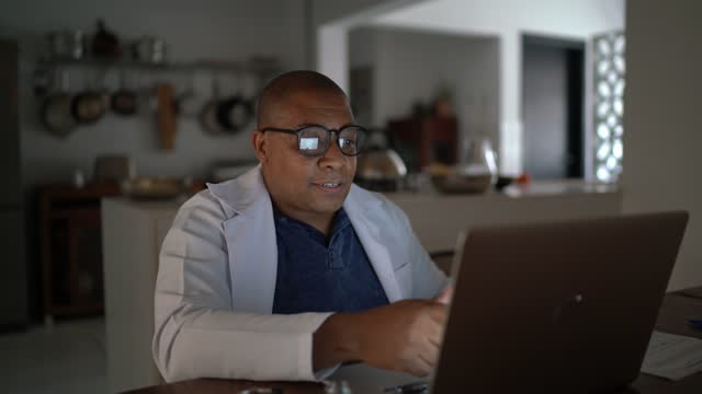 vídeos y material grabado en eventos de stock de doctor haciendo una consulta en línea por video chat en casa - adulto de mediana edad