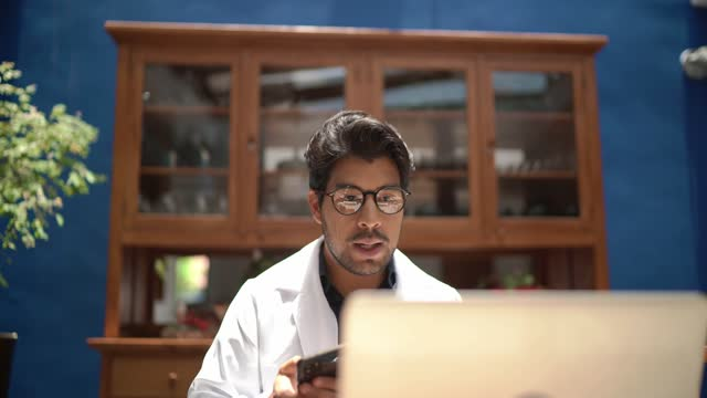 doctor making an online consultation by video chat - visit stock videos & royalty-free footage