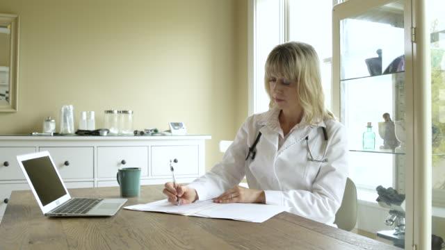 vídeos y material grabado en eventos de stock de a doctor making notes in on office - una sola mujer madura