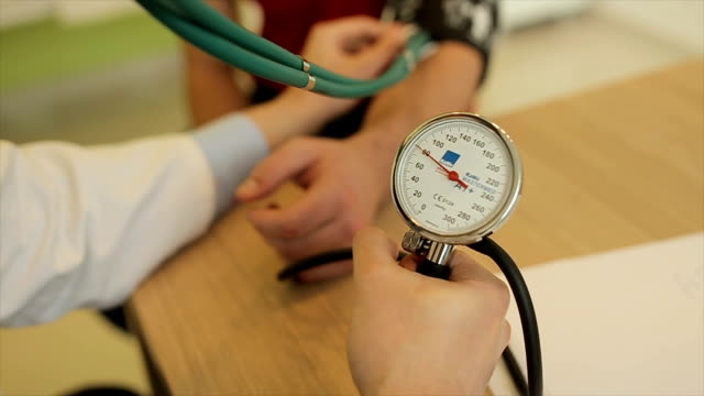 Doctor measuring patient blood pressure.Close up