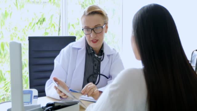 vídeos de stock, filmes e b-roll de reunião de médico e explicando a medicação a paciente mulher em seu escritório em hospitais - prancheta