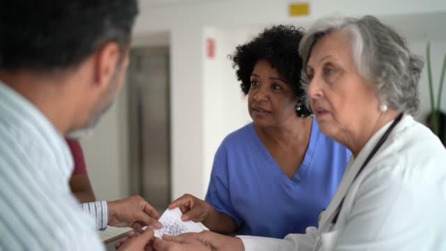 vídeos de stock, filmes e b-roll de médico, enfermeiro e pacientes na secretaria do hospital - secretária