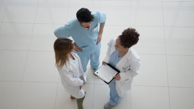 doctor, nurse and surgeon talking about a case while holding a medical record at the hospital - medical building stock videos & royalty-free footage