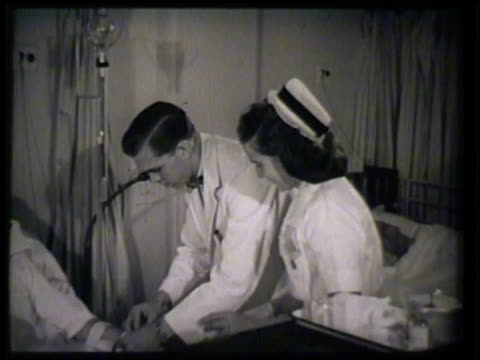 doctor nurse in hospital ward tending to patient lying in bed male doctor wrapping patient's forearm female nurse preparing needle shot doctor... - forearm stock videos and b-roll footage