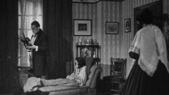 1943 RECREATION Doctor on a house call examining coughing patient who is lying on a parlor chaise lounge, and conversing with distraught relative in the 1840s / United Kingdom