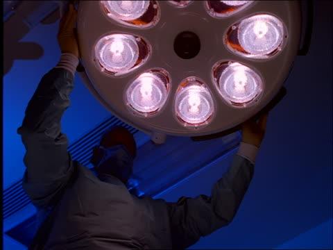 Doctor or nurse pulling back light in operating room