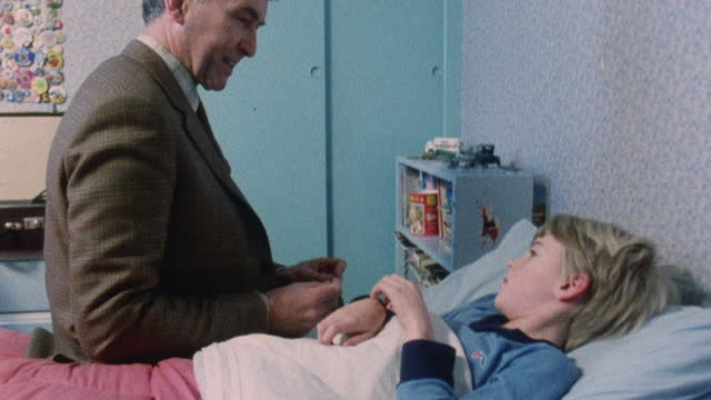 1983 montage doctor paying house call on young patient / london, england - visita a domicilio video stock e b–roll