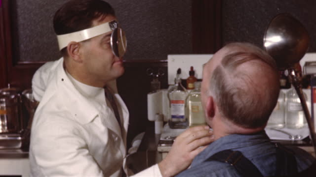 stockvideo's en b-roll-footage met 1955 ms doctor performing medical examination on patient/ usa - 1955