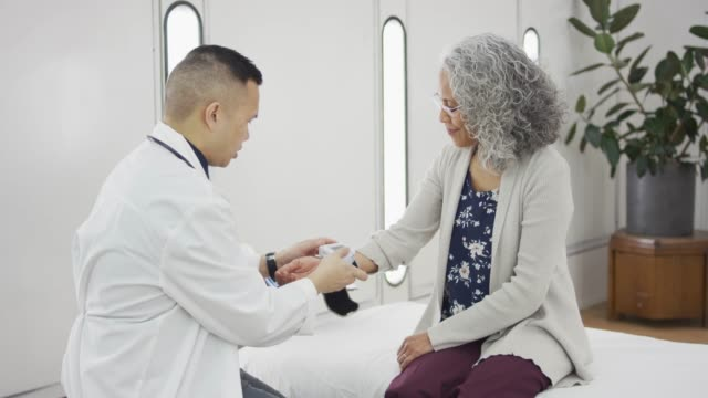 doctor placing blood pressure device on senior female patient - pacific islander doctor stock videos & royalty-free footage