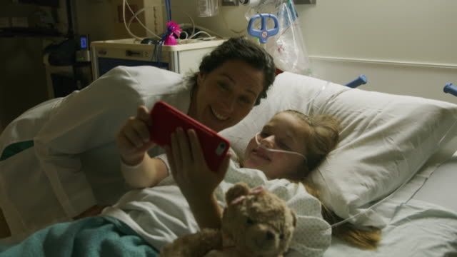 doctor posing for cell phone selfie with girl in hospital bed / salt lake city, utah, united states - krankenhaus stock-videos und b-roll-filmmaterial