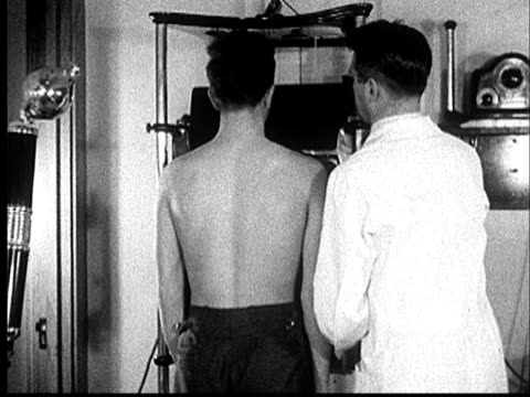 1935 MS doctor positioning young man for chest x-ray and lining up x-ray apparatus/ AUDIO