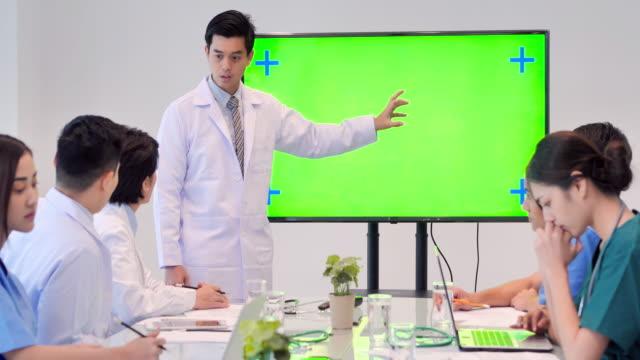 arzt präsentiert auf dem grünen bildschirm während eines treffens und junge praktikanten hören arztvortrag während der medizinischen konferenz.medizinische ausbildung, gesundheitsversorgung, medizinische ausbildung, menschen und medizin konzept. educa - medizinisches röntgenbild stock-videos und b-roll-filmmaterial