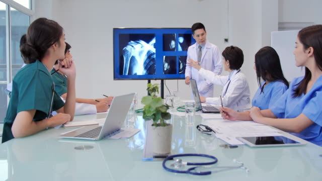 doctor presenting x-ray during a meeting and young interns listening to doctor's lecture during medical conference.medical workers working in conference room.medical education, health care, medical education, people and medicine concept.education topics - medical student stock videos and b-roll footage