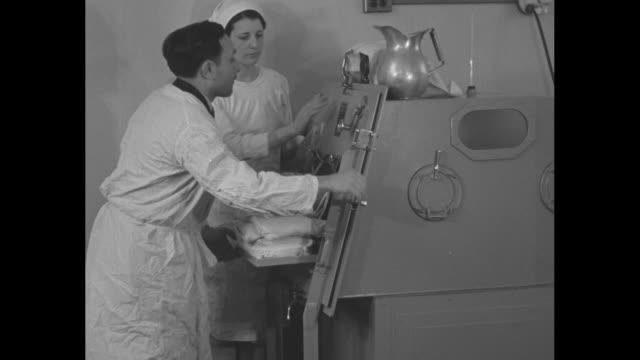 doctor pushes young earl potter into artificial respirator machine as nurse stands by / doctor's finger pushes button to start the artificial lung... - machine valve stock videos & royalty-free footage