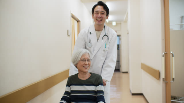 医師は病院で車椅子の患者を押します - 気にかける点の映像素材/bロール