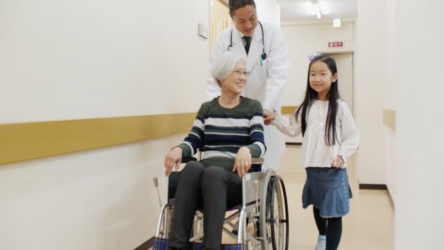 医師は孫娘を伴って病院を通って患者を押します - 病院点の映像素材/bロール