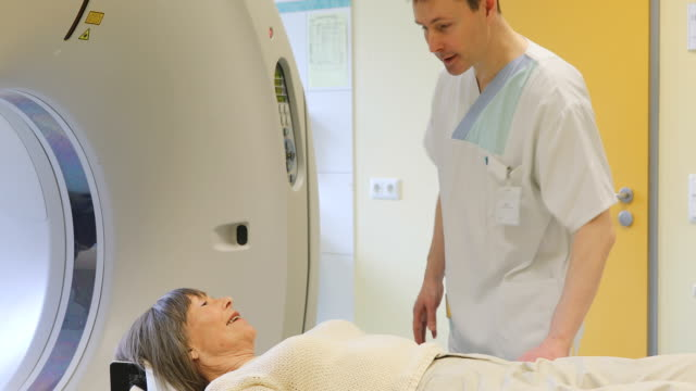 Doctor raising patient lying on CAT scan machine