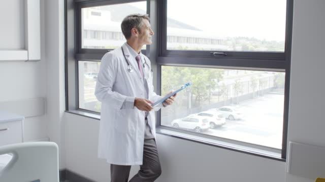 arzt lesen zwischenablage durch fenster im krankenhaus - dreiviertelansicht stock-videos und b-roll-filmmaterial