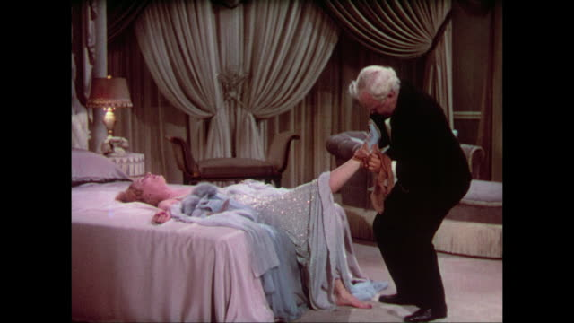 1937 doctor (charles winninger) removes stockings from an inebriated woman (carole lombard) - stockings stock videos & royalty-free footage