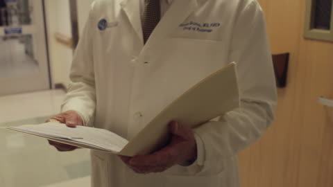 cu tu ms doctor reviewing patient's chart and walking down hospital hallway / portland, maine, usa - file stock videos & royalty-free footage