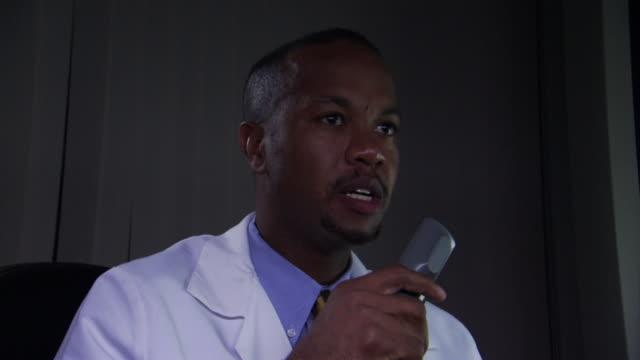 vidéos et rushes de cu doctor reviewing x-rays and speaking his notes on recorder / burlington, vermont, usa  - chemise et cravate