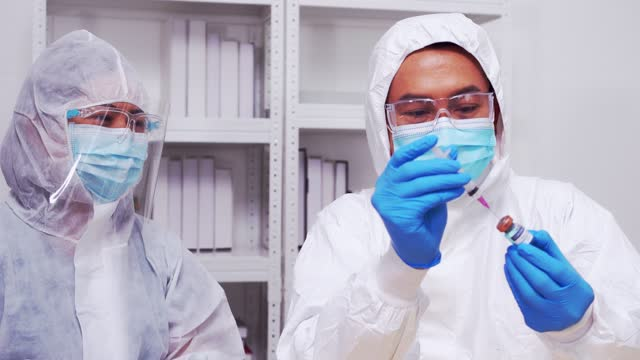 stockvideo's en b-roll-footage met arts, wetenschapper, onderzoeker hand in blauwe handschoenen met griep, mazelen, coronavirus, covid-19 vaccin ziekte voorbereiden op menselijke klinische proeven vaccinatie schot. - rabiës