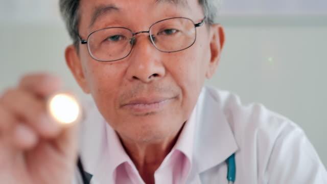 stockvideo's en b-roll-footage met doctor senior mannen onderzoeken patiënten oog met penlight in het ziekenhuis. medisch, onderwijs, technologie, wetenschap, gezondheidszorg, mens en geneeskunde concept. medische consultatie. arts en patiënt consultatie - netvlies