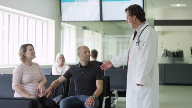 Doctor shaking hands with couple in corridor