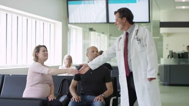 vídeos y material grabado en eventos de stock de doctor estrechando las manos con pareja en la sala de espera - sala de espera característica de edificio